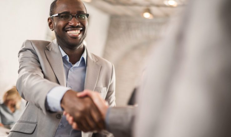 Happy African American businessman shaking hands with his unrecognizable colleague.